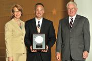 Carol Clark and Berkwood Farmer present Jeff Hoagland with an award for his induction into the 40 Under 40 Hall of Fame.