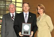 Carol Clark and Berkwood Farmer present Secretary of State Jon Husted with an award for his induction into the 40 Under 40 Hall of Fame.