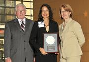 Carol Clark and Berkwood Farmer present Madeline Iseli, VP of advancement for Sinclair Community College, with an award for her induction into the 40 Under 40 Hall of Fame.