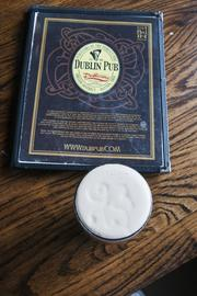 The Dublin Pub menu and a pint of Guinness with the clover leaf design in the frothy head of the beer.