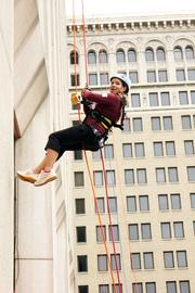 Katie Kenney walks backwards down a building.