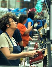 Rhonda Magoto tests a newly made hand mixer while working on the assembly line KitchenAid factory in Greenville.
