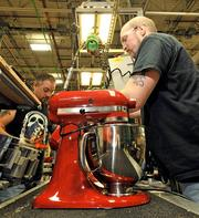 Travis Mamazza (left) and Joe Claxton work on mixers on the assembly line at the KitchenAid factory in Greenville.