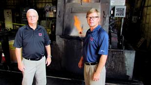 Poised for Growth: (Left to Right) Rick Young, sales manager, and Larry Gray, president of Dayton-based American Heat Treating, stand next to one of the company's furnaces. The company has added workers and is making investments as revenue climbs.