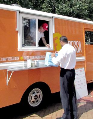 Interaction: A customer orders food from Fressa Truck, one of Dayton's food trucks, which often set up sites in different locations. The owners of food trucks have embraced social media to interact with customers.