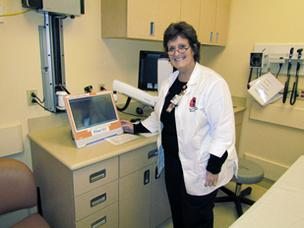 Translation Station: Pam Lamb, a clinical nurse educator in the Kettering Medical Center emergency department, stands beside MARTTI, a live interpreter computer. Kettering began using the service in July, which provides instant interpreting to handle a growing number of non-English speakers.