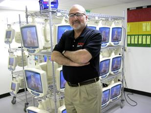 Smart Changes:  Lou Vilardo, president of Springboro-based PDI Communication System stands in front of the company's movable televisions, which are used in health care facilities. Vilardo reconfigured his facility last year to bring more manufacturing under his roof.