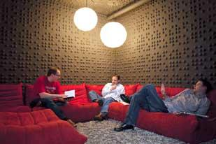 Fostering Creativity: Real Art Design Group in Dayton features a non-traditional office setting at its downtown location across from Fifth Third Field. Company executives say the look helps inspire workers.Executives sit and discuss a project.