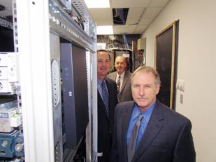 Strong Industry: The Ross Group in Beavercreek is among technology companies looking to hire. (Front to Back) Steve Woody, senior vice president and leader of a new division; Gary Codeluppi, senior vice president; and Mark Ross, CEO, stand in the company's server room.
