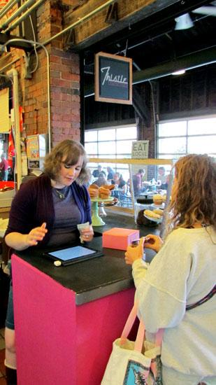 Using Technology:  Hilary Browning, owner and operator of Thistle Confections at the PNC Second Street Market in Dayton, uses an iPad and the Square app, which allows her to swipe credit cards and acts as her cash register.