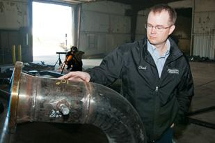Westcon Industries Area Manager Chad McKay looks over a piece of pipe which will be shipped to an oil refinery as welders work on the assembly of another section in the background.