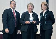 CFO honoree Sylvia Clasen of St. Leonard receives her award from  Kevin Weckesser of sponsor Brixey & Meyer and DBJ Publisher Carol  Clark.