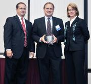 CFO honoree Tom Fath of Flowserve receives his award from  Kevin Weckesser of sponsor Brixey & Meyer and DBJ Publisher Carol  Clark.