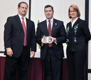 CFO honoree Seth Morgan of MLA Management Systems receives his award from  Kevin Weckesser of sponsor Brixey & Meyer and DBJ Publisher Carol  Clark.