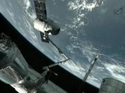 A robotic arm of the International Space Station is seen grasping the Dragon cargo vehicle In a television image from Earth orbit at about 8:45 a.m. MDT Friday, May 25.