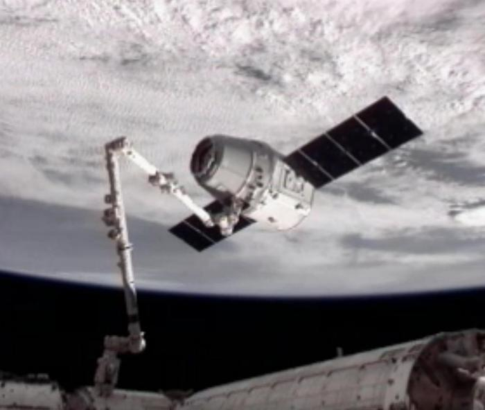 A robotic arm of the International Space Station is seen grasping the Dragon cargo vehicle In a television image from Earth orbit at about 8:30 a.m. MDT Friday, May 25.