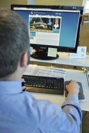 Doug Gieck, client care manager, reviews one of the listing pages online.