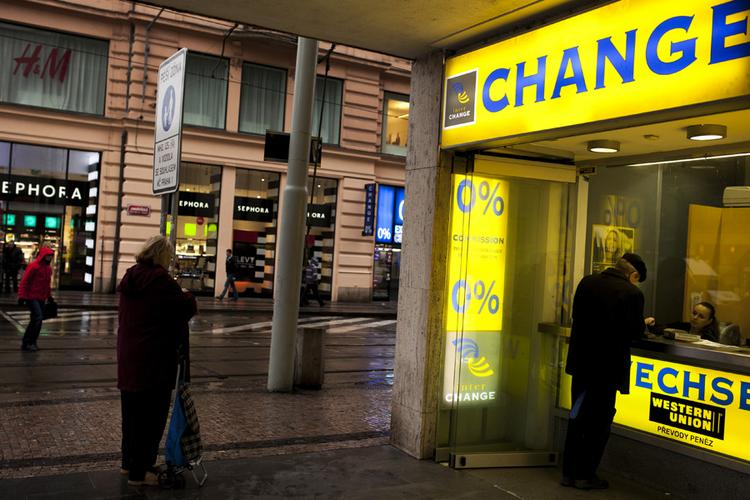 A customer uses a Western Union currency exchange to change money in Prague, Czech Republic, on Jan. 8, 2013.