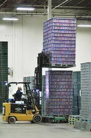 Kelly Henderson, Material Handler is removing finished product from the production line to prepare for shipment at Ball Metal Beverage Container in Golden.