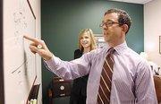 Michael Massey, financial adviser at Edward Jones, works with trainee, Joni Darr.