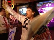 Mimi Bell passes out flags and signs at the Republican party at Sports Authority Field at Mile High.