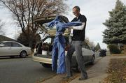 Grant Swanson, co-founder of GB3 Energy Solutions, cleans off his gear before heading into a Denver home to perform an audit for a bid.