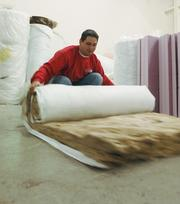 Insulation is rolled up to be put on a truck at GB3 Energy Solutions