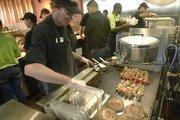 Employees cook up kabobs at Garbanzo Mediterranean Grill at Promenade at Denver West in Lakewood.