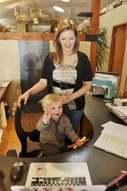 Carrie Odberg, director of first impressions, sits Brooks, Laura Love's (president and CEO) son in a front desk chair at the office of GroundFloor Media.