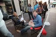 Kristina and Brit Welch get comfortable in line for H&M's grand opening in Denver Pavilions Thursday. Kristina, a student at University of Colorado Denver, does homework and Brit watches Netflix on his iPad.