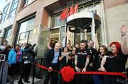 H&M staff, including U.S. H&M president Daniel Kulle (far left in blue shirt) and Jeremy DeCola, store manager (with scissors), cuts the ribbon for H&M's grand opening in Denver Pavilions.