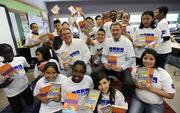 Mike Moore, tax partner, and Barry Amman, audit partner, at KPMG (middle) sit with Barrett Elementary fifth graders who just received books donated by KPMG.