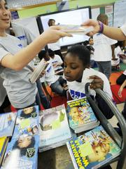 Kayla Sawyer, a fifth-grader at Barrett Elementary in Denver, checks out the new books distributed by KPMG volunteers. Each student in the school received two books. KPMG has fundraisers throughout the year in order to buy the books they hand out.