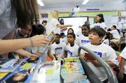 Fifth-graders Saint Alvarado, Kayla Sawyer and Elijah Wilson wait to receive their books from KPMG volunteers at Barrett Elementary. Each student in the school received two books. KPMG has fundraisers throughout the year in order to buy the books they hand out.