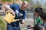 """KPMG volunteers for Earth Day at Sandoval Elementary School helping the kids plant seeds in an effort to teach the  """"cycle of life"""". Matt Blei from KPMG helps the kids water the newly planted seeds."""