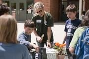 """KPMG volunteers for Earth Day at Sandoval Elementary School helping the kids plant seeds in an effort to teach the """"cycle of life"""". Erin Casey from KPMG helps the kids."""