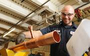 Eric Bigham works with copper piping at RK Mechanical. He has worked there for seven months.