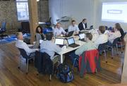 The Point B Inc. staff gathers for an early morning meeting. In 2008, Point B implemented an employee stock ownership plan.