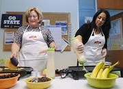 Robyn Fleischman, executive assistant, and Doris Lane, executive assistant, at Comcast make pancakes for a pancake breakfast benefiting Mile High United Way.