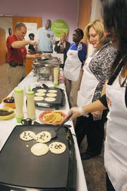 Chris Shea, vice president of marketing & sales gets breakfast at work served by co-workers. The money raised goes to  Mile High United Way.