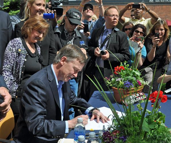 Gov. John Hickenlooper signs the film-incentives bill at High Noon Entertainment on Friday, May 18, 2012. Standing directly behind him is state Sen. Linda Newell, D-Littleton, who co-sponsored the bill.