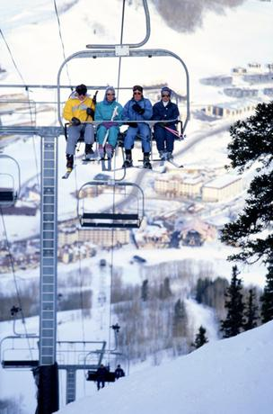 Skiers ride a chairlift at Colorado's Crested Butte Mountain Resort.