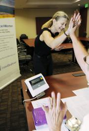 Claudia Opsal, senior executive assistant at UnitedHealthcare, weighs in at a good weight for her and high-fives Marilyn Macdonald of Weight Watchers. September 2011