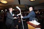 Fred Bauman, Rothgerber, Johnson & Lyons, receives an autographed hockey stick from Kurt Schwartzkopf, Kroenke Sports & Entertainment, during a drawing at the VIP reception at the DBJ's Connections 2011-2012 event at the Pepsi Center.