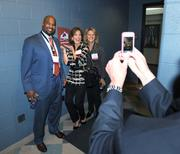 Richard Lewis, RTL Networks; Margaret Kelly, Remax; and Larissa Herda, TW Telecom; take photos during the VIP tour of the Avalanche locker room during the DBJ's Connections 2011-2012 event at the Pepsi Center.