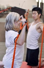 Bridgepoint Education Inc. ranked No. 3 in the x-large-size business category. Robert Tanaka, a trainer for 24 Hour Fitness, leads a free fitness class for Bridgepoint Education staff. Claire Holton-Zenner takes part.