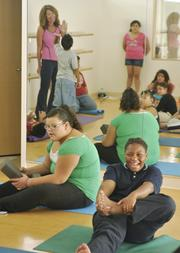Diane Dennis, a student exercise instructor at The Children's Hospital (in pink), gives a high five during the weight management clinic for kids. October 2011