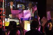 Early in the night, supporters of Gov. Mitt Romney wave signs and flags as they watch the results.