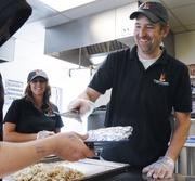Tom McDonald, director of production and partner, from Fireside Production, serves hashbrowns at Urban Peak while colleague Tammie Waddell, marketing manager, looks on. The food was purchased, cooked and served by Fireside Production.