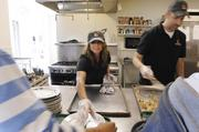 Tammie Waddell, marketing manager, along with Tom McDonald, director of production and partner,  at Fireside Production, serve breakfast at Urban Peak. The food was purchased by Fireside and Waddell made 50 breakfast burritos the night before in her home. The burritos were a big hit with the youth.
